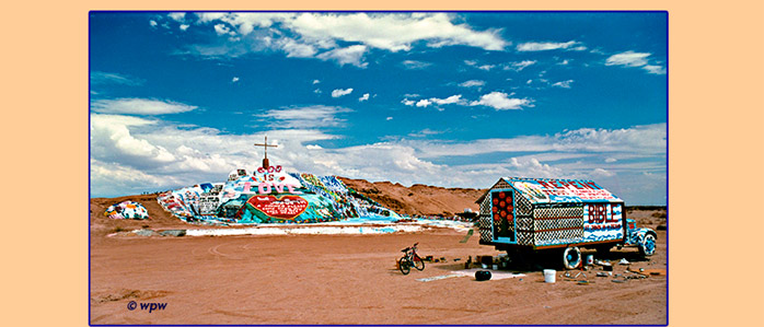 <1996 panorama photo by Wolf P. Weber depicting front view of Salvation Mountain and Leonard Knight's Parading Truck>